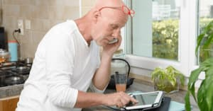 A middle-aged man stands in the kitchen and looks at his iPad and talks on the phone