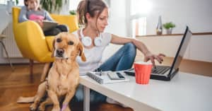 A woman sits on the floor with her dog looking at her finances on her computer, while her daughter sits behind her in the background