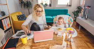 A woman looks at her home finances and investments on her computer while her baby sits in a highchair next to her