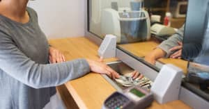 A woman withdraws cash from her investment account at the bank