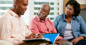 A woman cheerfully discusses family finances with her son, while her husband looks on