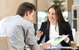 A smiling counselor shows a client a paper with a chart