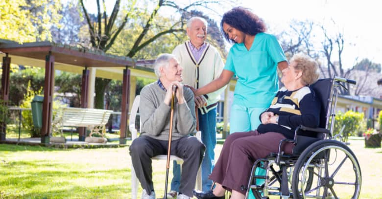 A nurse visits with several nursing home residents