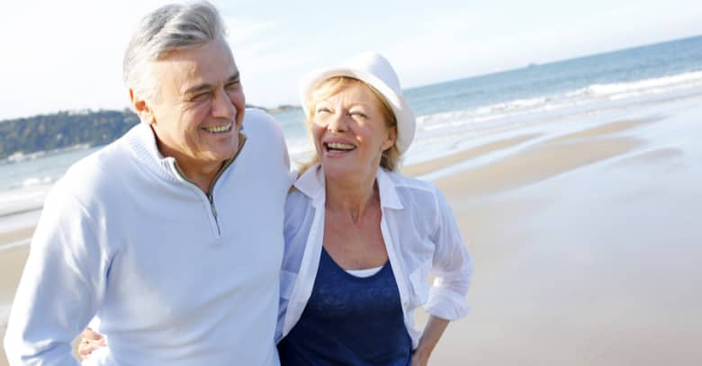 A senior couple enjoys a walk on the beach