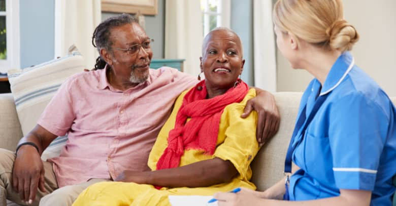 A nurse discusses care options with a senior couple