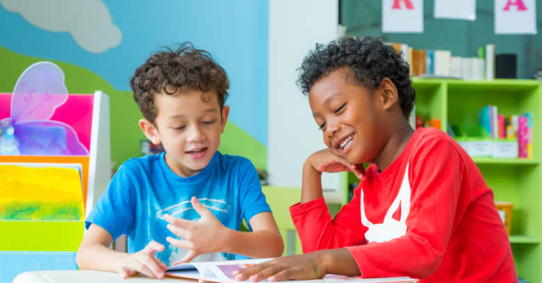 Two boys share a book at after-school care.