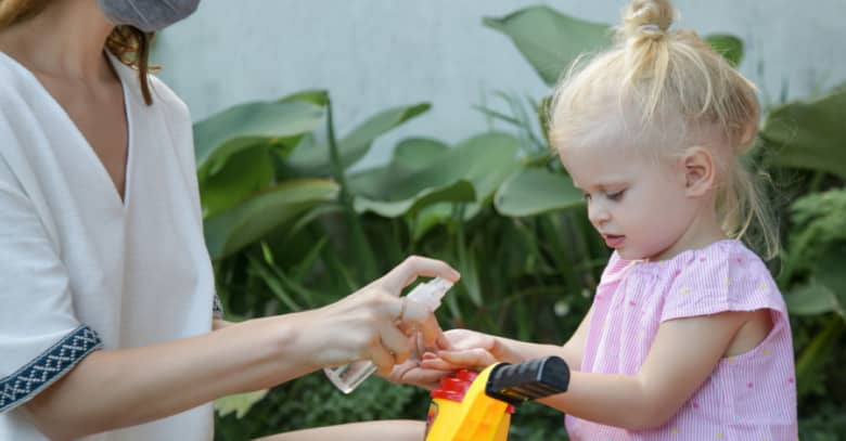 a child care provider dispenses hand sanitizer to a preschooler riding a tricycle