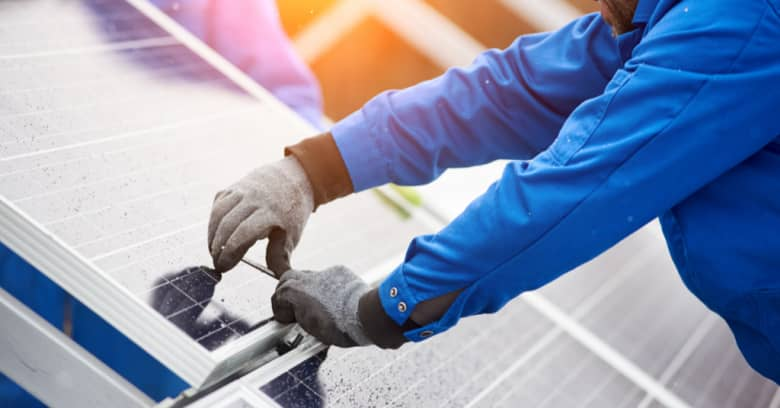 A worker installs solar panels on a building