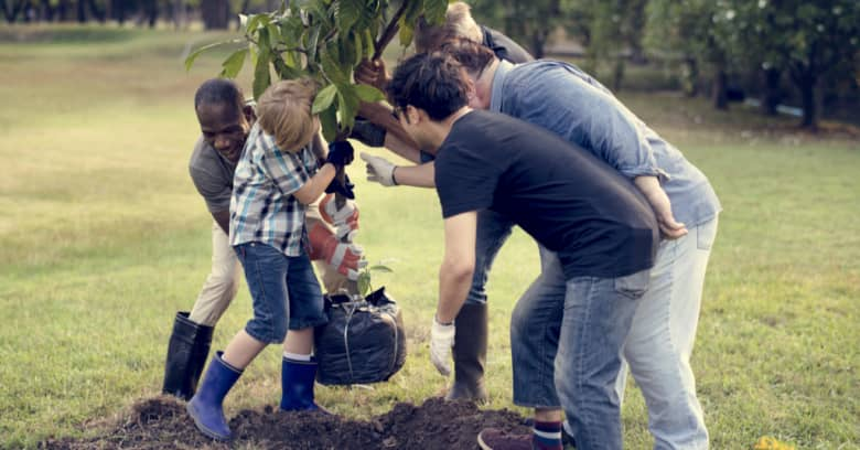 A diverse group of people plant a tree
