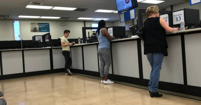 People are shown conducting business at their local DMV