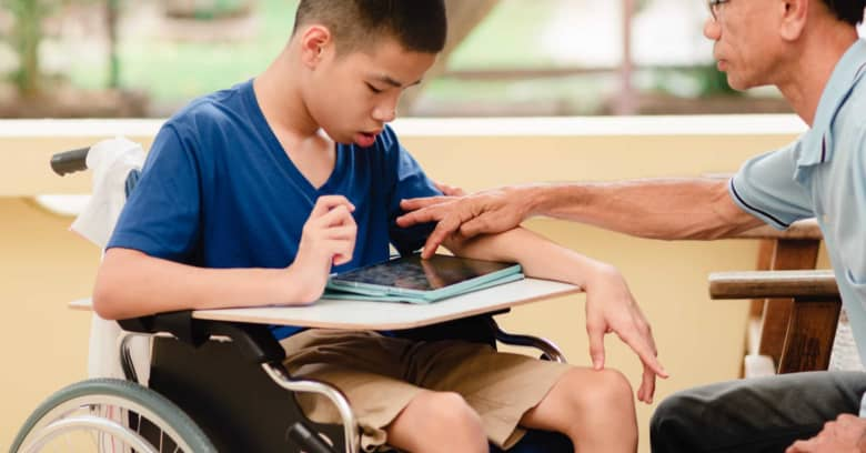 A student using a wheelchair looks at a computer tablet with his caretaker
