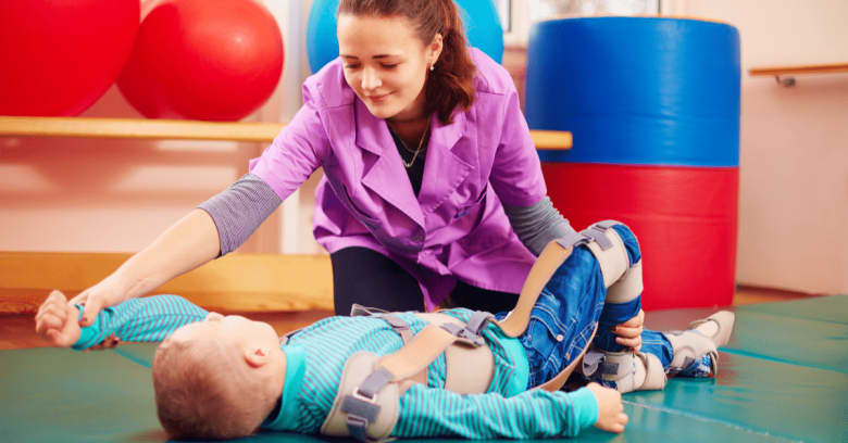 A physical therapist works with a boy who has special needs