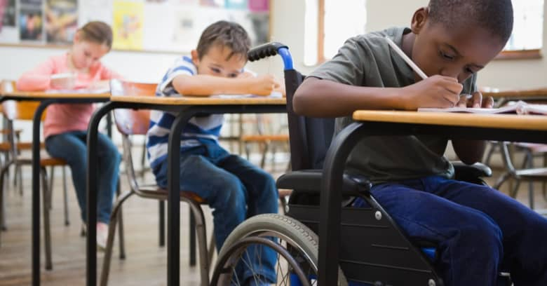 A child who uses a wheelchair works hard in his classroom