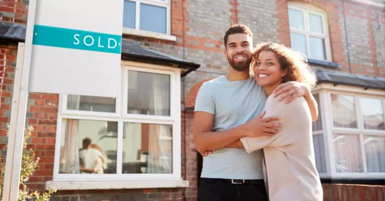 A young couple stand in front of their first home purchase with a 'sold' sign in the front yard.