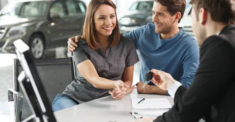 A young couple looks happy as they meet with a car salesperson to discuss their car-buying options
