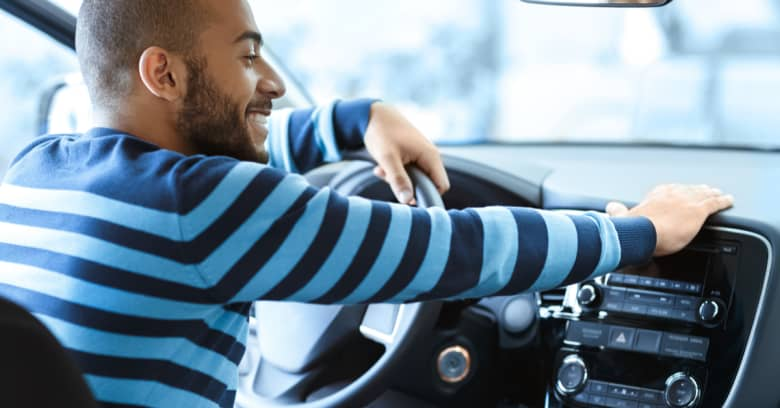 A smiling man sits in his new car and admires it
