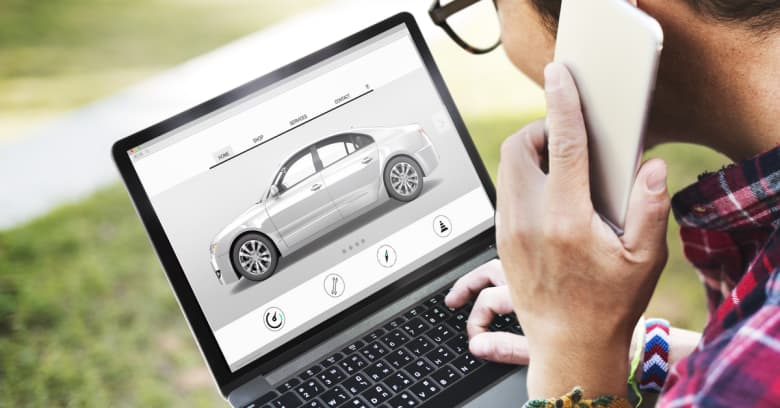 Looking over a man's shoulder, you can see he is researching cars for sale on his computer and he is also talking on the phone to ask about a car he sees