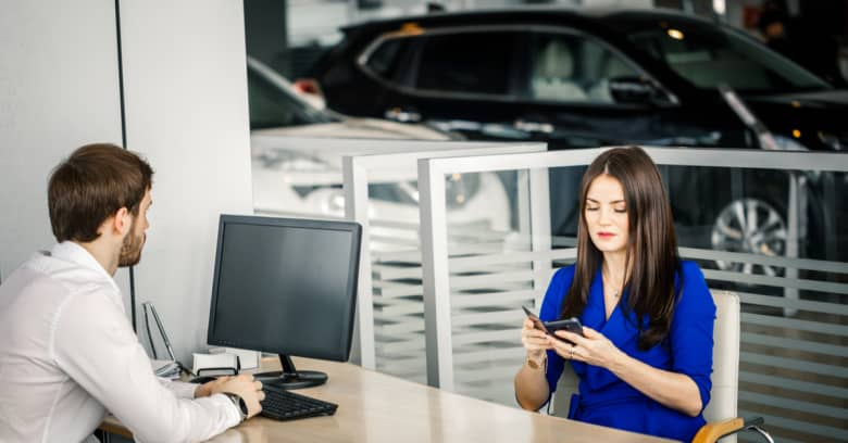 a woman sits at a desk at a car dealership with a salesman as she negotiates the price of a car she's interested in buying
