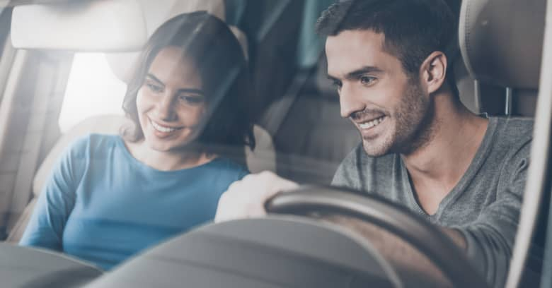 a young man prepares to test drive a new car while his girlfriend sits in the passenger seat