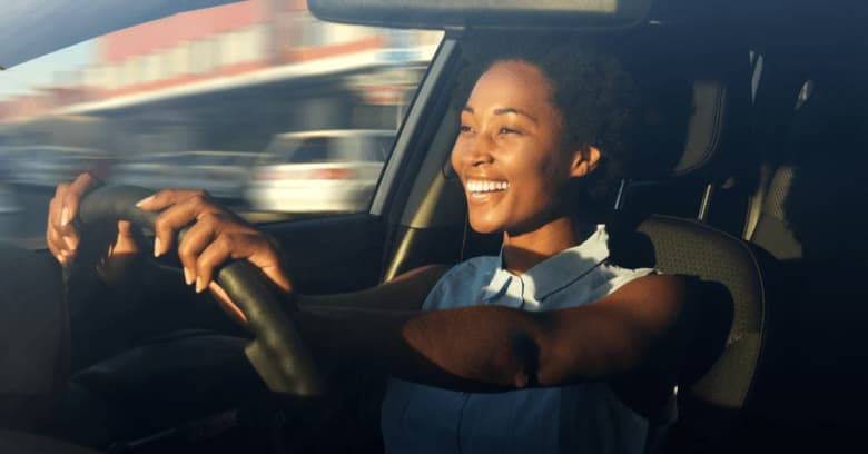 A young woman is happy to be driving her new car.