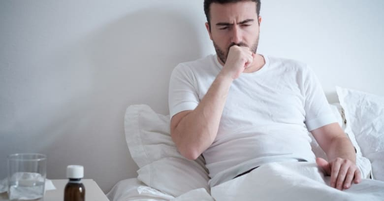 A man sits up in bed coughing as he stays home sick from work because of coronavirus.