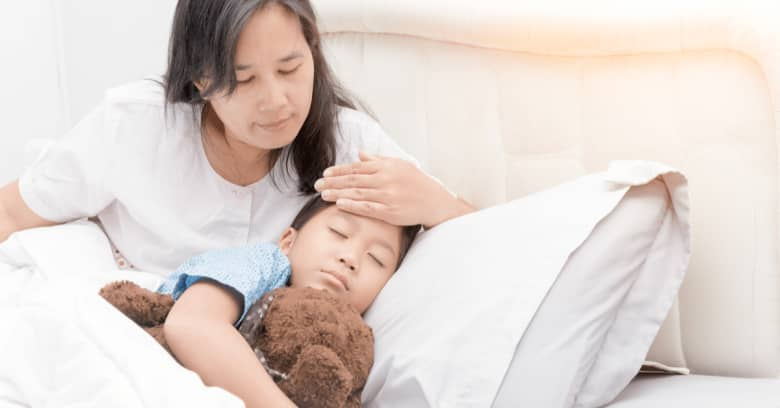 A mother places her hand on her son's forehead to check his temperature while he sleeps.