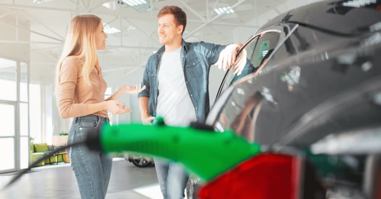 A man and woman are in a car showroom, talking while looking at a green electric car with a charging cord attached