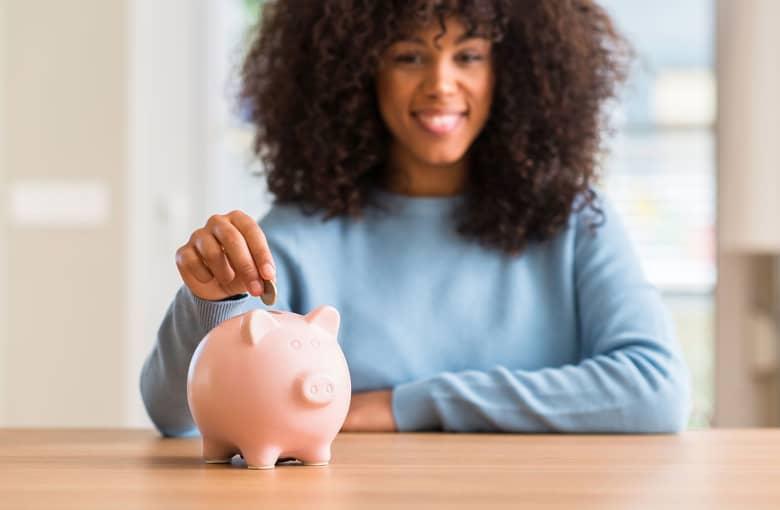 A woman drops coins into a piggy bank
