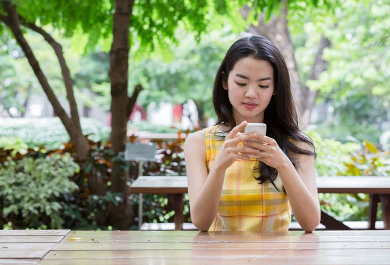 A woman sits at a picnic table outside and looks at her phone.