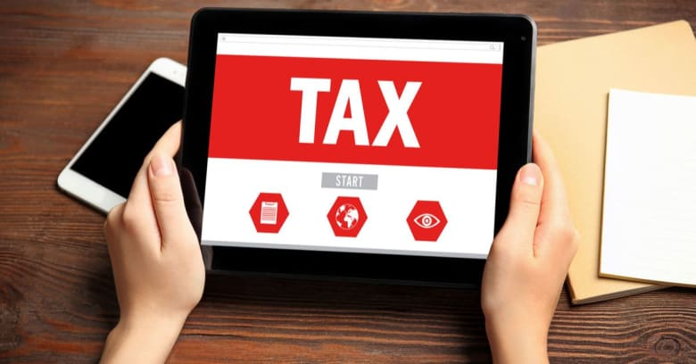 A person is holding a tablet and preparing to start the tax-filing process.
