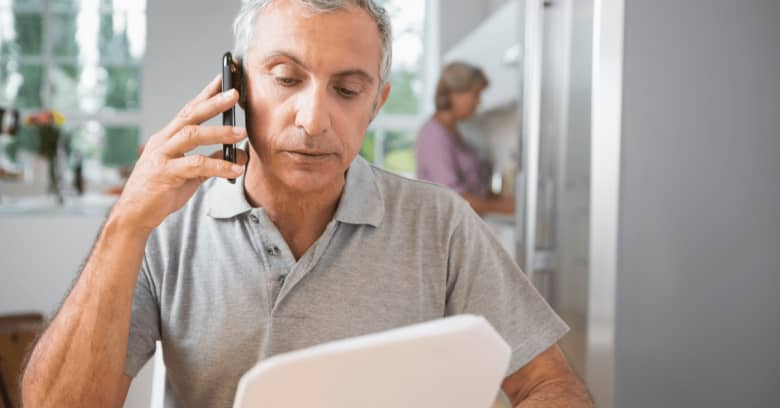 A man speaks on the phone with his insurance agent