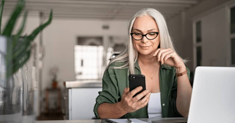 A woman looks at phone and smiles to see that she's been given a car insurance rebate
