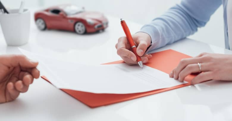 A young woman is signing documentation for her car loan.