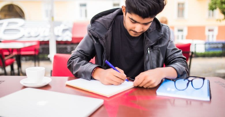 A young man writes in his notebook.