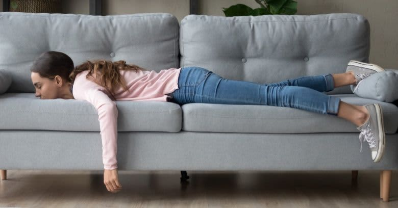 A woman lies on the couch.