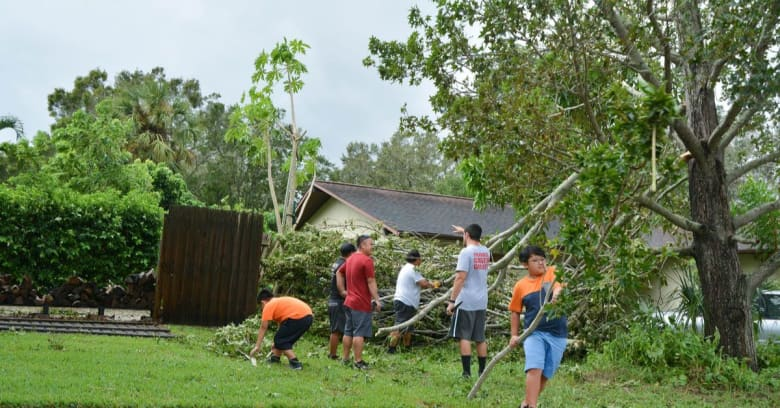 A group of neighborhood helpers remove debris from a yard after a hurricane