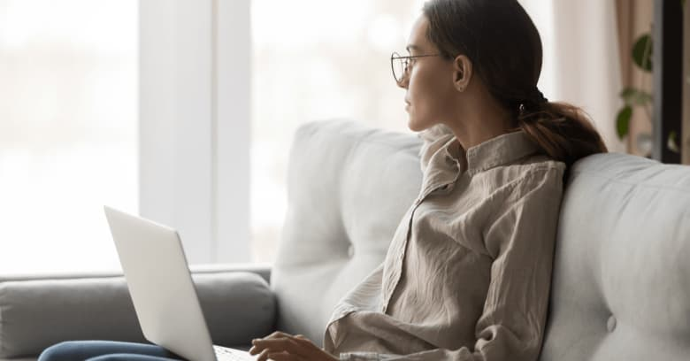 a woman sits on the couch with a laptop computer on her lap. She is gazing distractedly out the window.