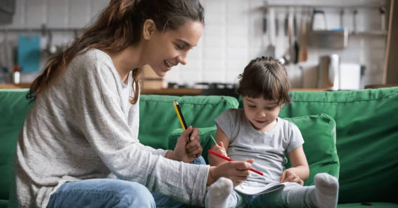 a woman and a little girl are sitting on the couch drawing pictures
