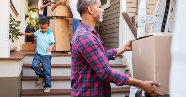 family members move boxes of personal items into their new home