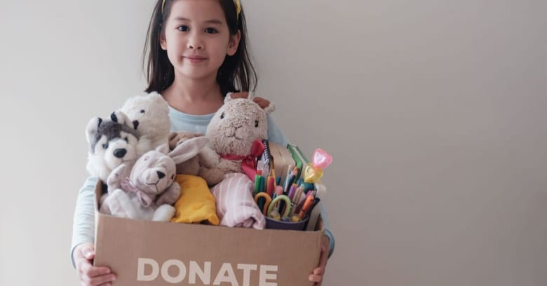 A young girl is preparing to move with her family by gathering up some of her belongings and donating them