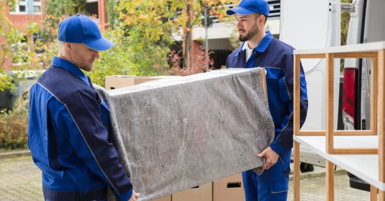 Two men, who are professional movers, move items into a new home