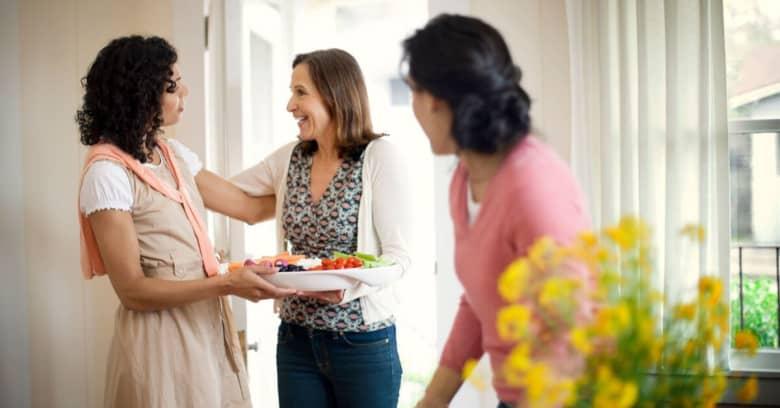 a woman welcomes some new neighbors to the neighborhood