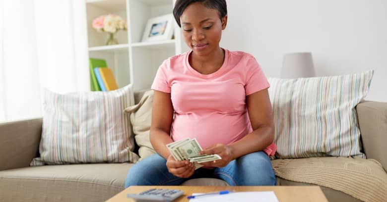 pregnant woman counting money and budgeting