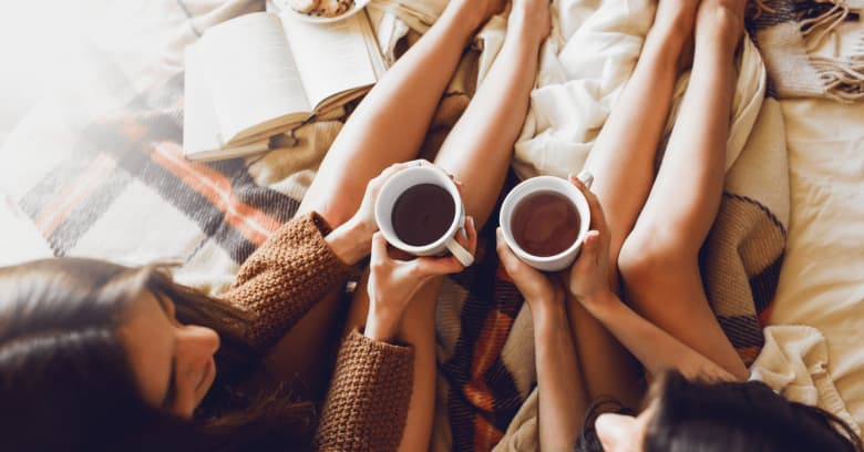 Two sisters sit on the bed with a book nearby as they enjoy a cup of tea together