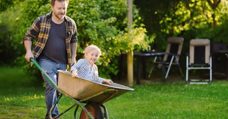 a man pushes his son in a wheelbarrow in the backyard