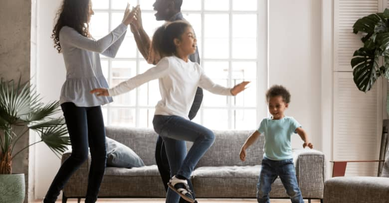 a family enjoys dancing together in their living room as they stay inside during the coronavirus quarantine
