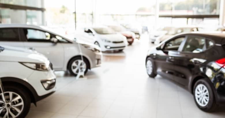 A row of new cars is seen at a dealership