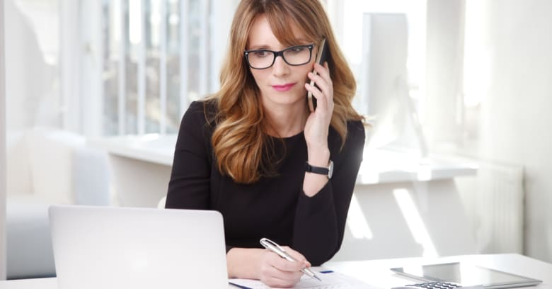 A woman makes some phone calls while working with numbers on her computer to see if she could benefit from an interest rate cut