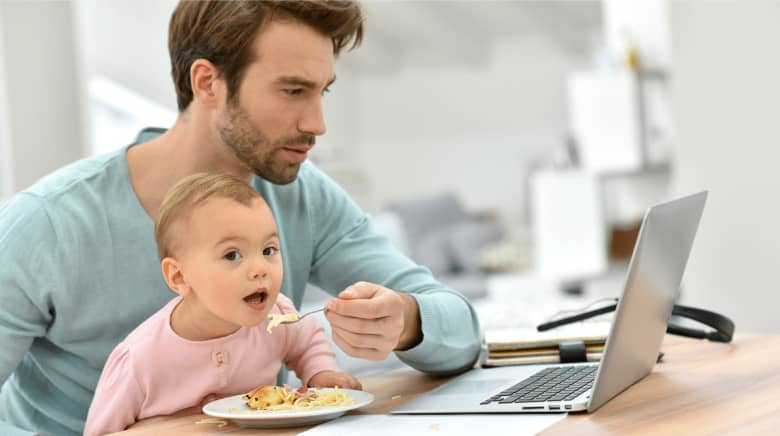 A man is working on his laptop and trying to feed his baby at the same time