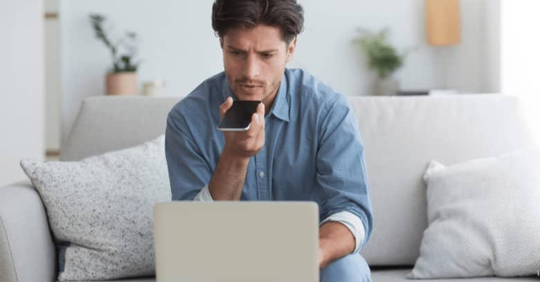 a man sits in front of his computer speaking into his phone while looking concerned